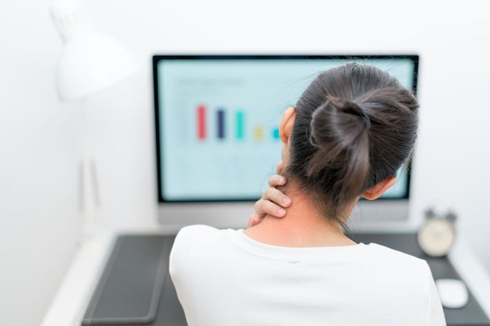 lady in front of computer holding neck